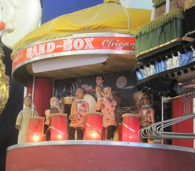 Bandbox structure with dolls inside it with instruments