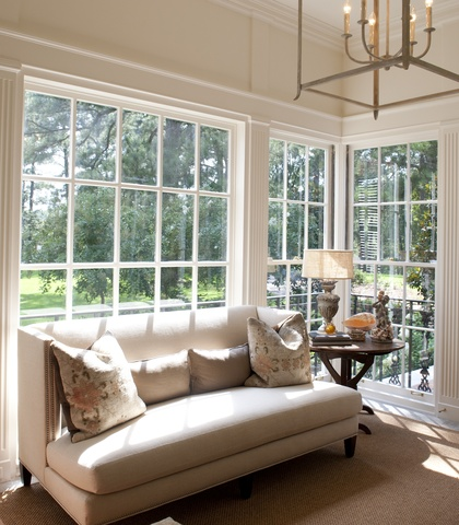 sunroom with large windows overlooking a backyard, a beige sofa with 4 pillows, a wooden side table holds a lamp and two small sculptures