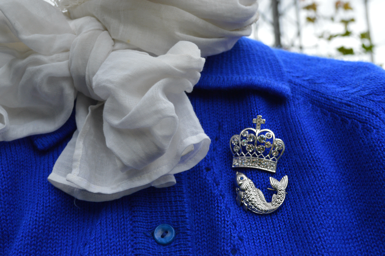 brooch, blue, silver, white scarf, fish, crown, cardigan