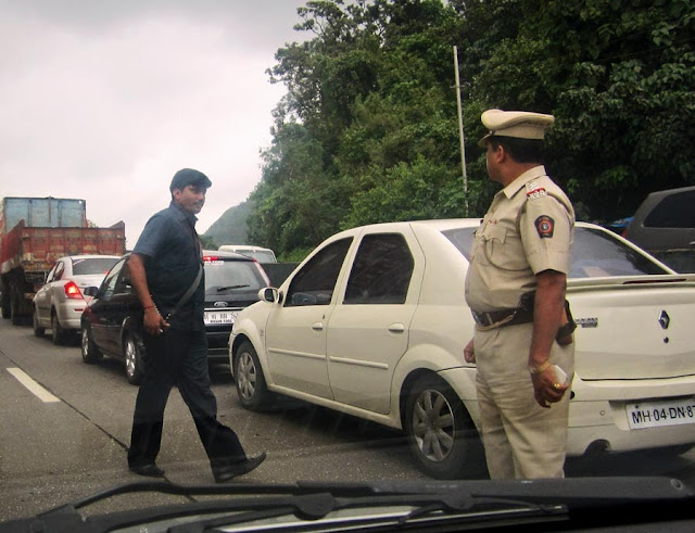 policemen in khaki helping politicians clear traffic jams