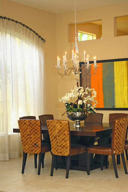 modern wooden dining table and chairs with a chandelier and beautiful flower centerpiece