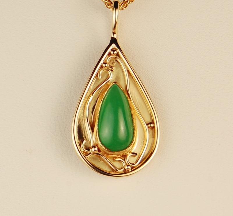 teardrop shaped green stone and pendant with wire and bead decorations