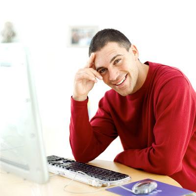 Chico sonriente delante de un ordenador
