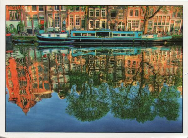 reflections of houses barges and trees in a canal
