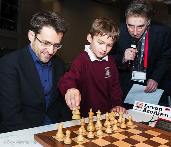 Un jeune joueur d'échecs suggère 1.Cf3 comme premier coup à Levon Aronian, sous le regard de l'organisateur et maître international Malcolm Pein - Photo © Ray Morris-Hill