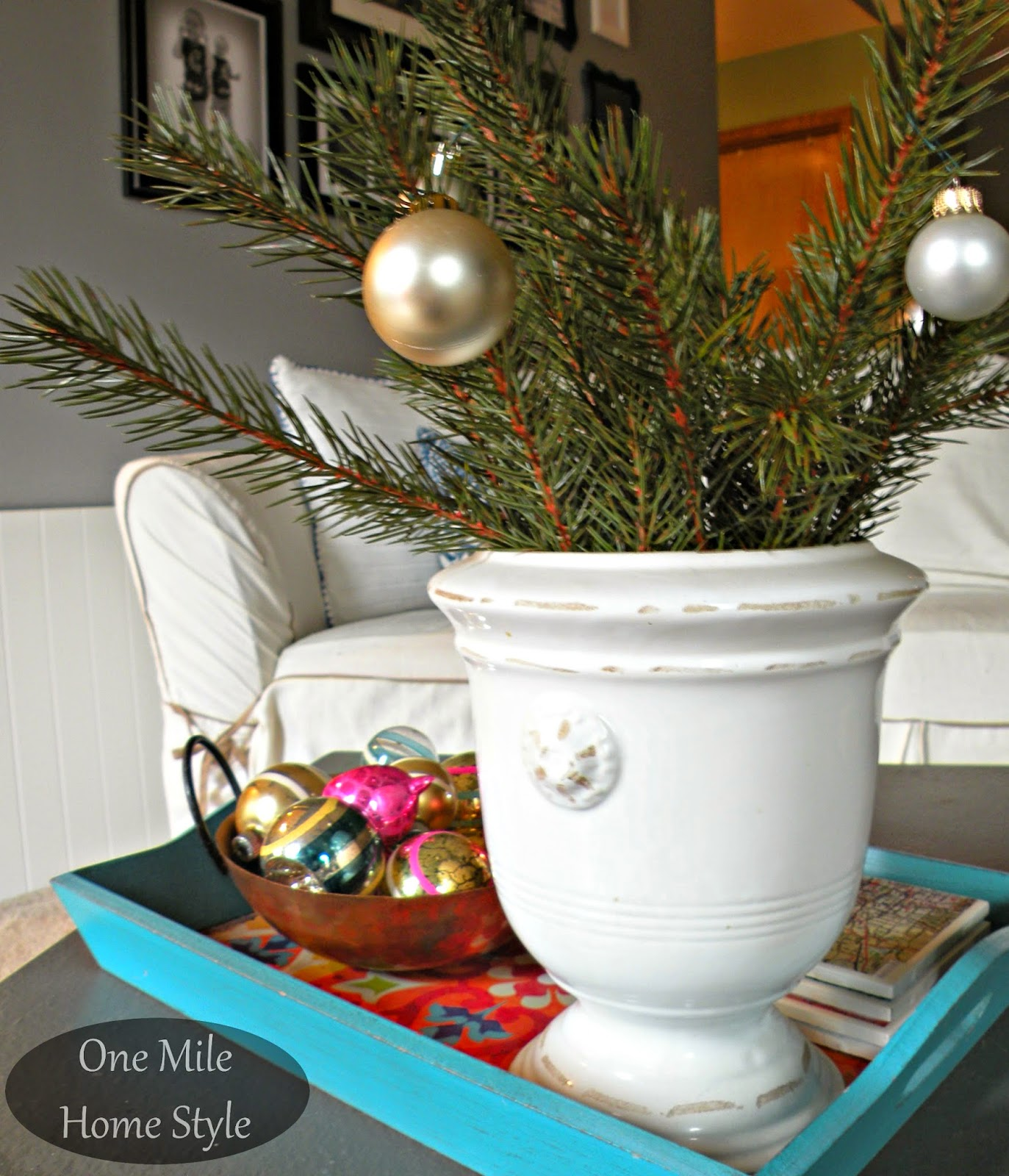 Christmas greenery with a copper bowl of vintage Christmas ornaments