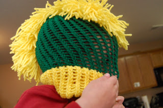 boy playing with a knit mohawk hat