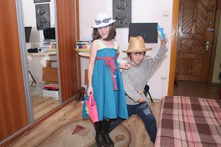 Szöveg: Pózolunk. Kép: A két kisebb gyermek képe. A fiúcska igazi cowboy díszben, pisztollyal támadó állásban, a leányka igazi kis hölgyként: kék szalagos fehér kalap, hevenyészett türkíz ruha bordó pánttal, kis táskával a kezében.