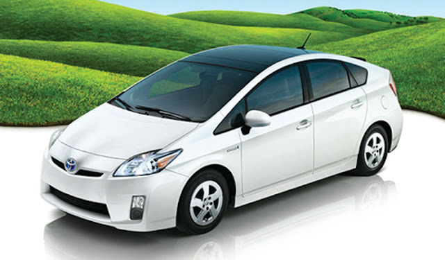 Front three-quarters view of white 2012 Toyota Prius next to green rolling hills