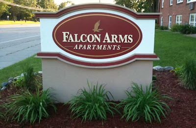 Nicely made oval sign with large letters reading Falcon Arms Apartments