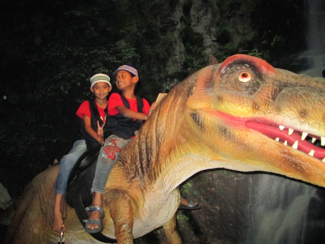 Children from Rumah Titian Kasih riding the T-Rex at Dinoscovery