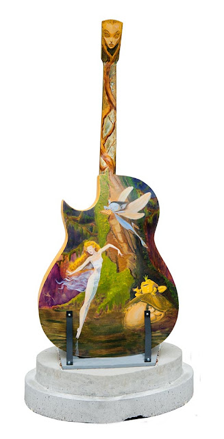 a large wooden guitar painted by a local artist with a scene from the woods with fairies, downtown Orillia