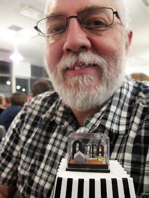 A man behind a  small display box containing the letters 'AMEA', and a tiny cottage and windmill, displayed on an upturned popcorn container.
