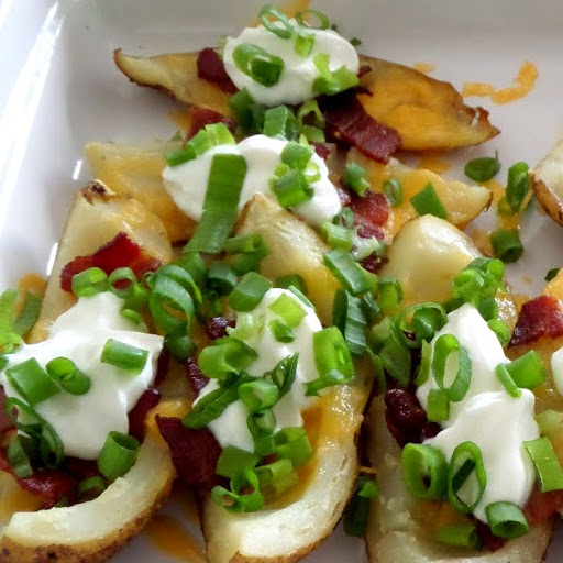 Loaded Baked Potato Skins:  Warm potato skins loaded with cheese, bacon, sour cream, and green onions.  A delicious gameday snack.  #footballsnack