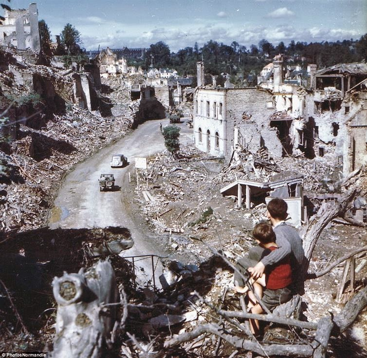 24 Rare Historical Photos That Will Leave You Speechless - The aftermath of D-Day as two boys watch from a tree while American soldiers drive through Saint Lo in France.