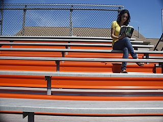 A girl reads a book outdoors at a stadium