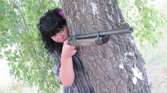 Chica detrás de un árbol a punto de dispararle a alguien con un rifle   Ximinia