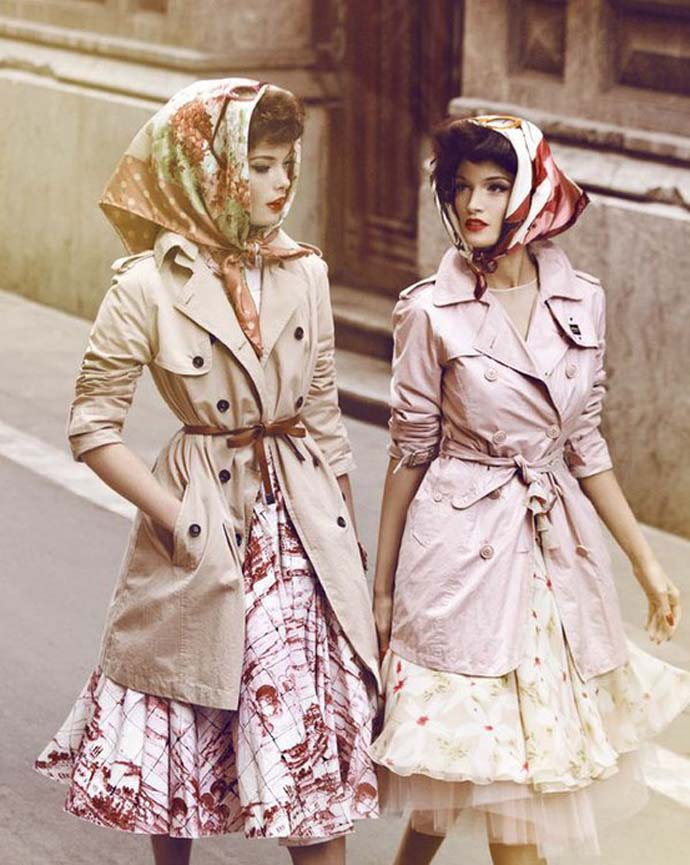 Two women dressed in a retro style wearing dressed and trench coats