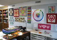 DIY Quilt studio design wall with a variety of quilts and projects on it