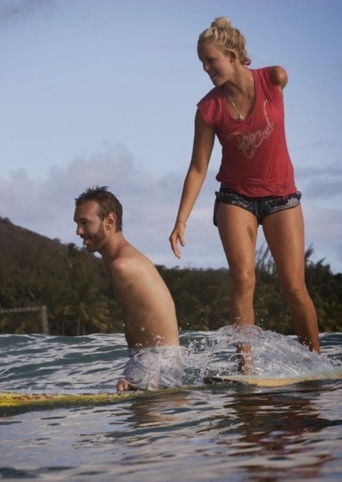 man and woman surfing, both have one arm amputated
