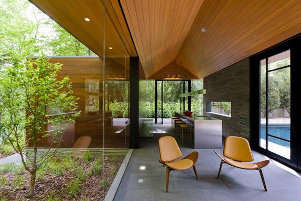 rumah paviliun dengan dinding kaca dan interior organik