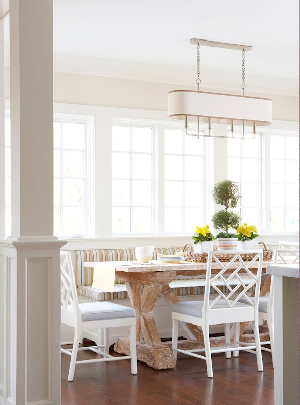 Breakfast nook with banquette seating, a chandelier, a reclaimed wood table surrounded by white chairs, and casement windows