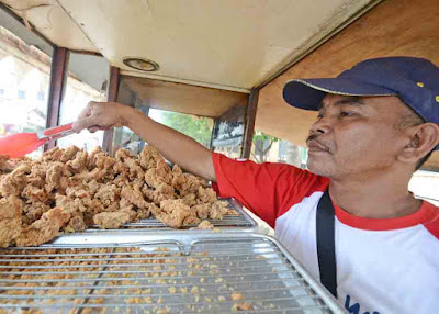 MENJAGA HANGAT : Sulaiman meracik sendiri ayam bikinannya. Di dalam gerobaknya ini sengaja dipasang lampu untuk menjaga ayam tetap hangat karena ketahanannya hanya sampai empat jam saja.  FOTO MARSITA/PONTIANAKPOST