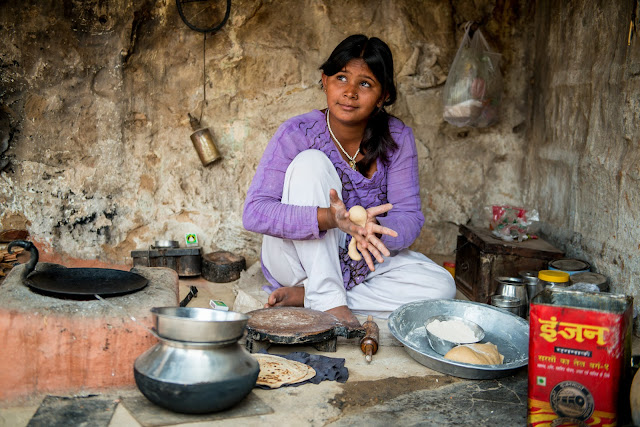A young child in a small village in Rajasthan, India making chapati for lunch