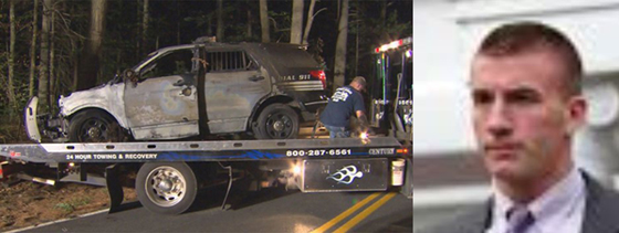 Bryan Johnson's (right) police SUV was towed away after the fire and crash, Sept. 2, 2015. (WBZ-TV) Investigators say Johnson made up a claim in September that a gunman fired at his cruiser before it crashed into a tree and caught on fire