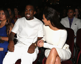 Kim Kardashian with boyfriend Kanye West sitting in their seats