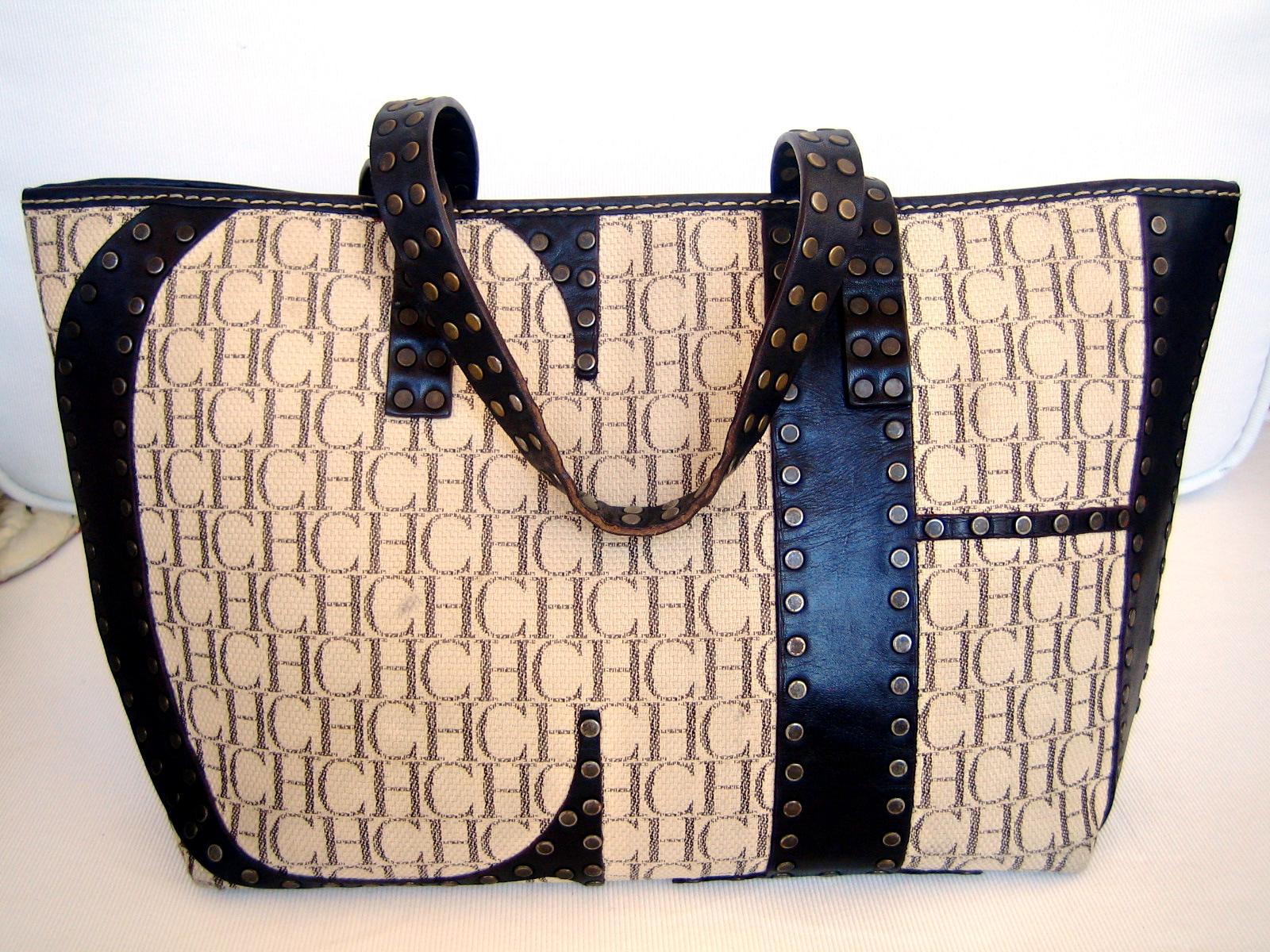 Half shopping así se denomina a este bolso de Carolina Herrera, todo un clásico de la firma, que lleva el logo de CH en piel con tachuelas;