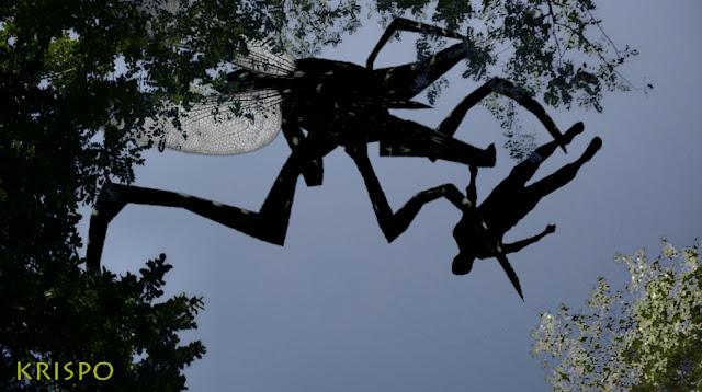 insecto gigante llevando un humano atrapado