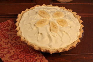 banana cream pie on wood table with red napkin