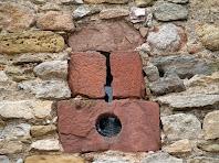 Detall de la finestra d'espitllera amb una rodona per a apuntar, al mur de llevant de la Torre de Don Carles