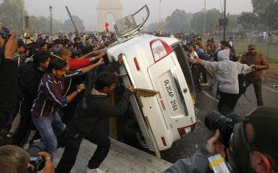 penunjuk perasaan menolak sebuah kereta dalam tunjuk perasaan membantah seorang pelajar wanita dirogol di New Delhi semalam
