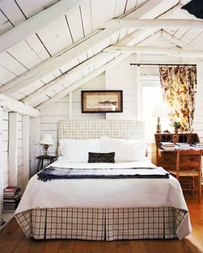 rustic country bedroom a a plaid slip covered headboard, roof line post beam ceiling, rustic wood desk, chair and wood floor