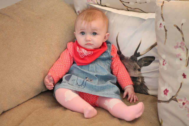 baby wearing denim dress and polka dot long sleeve vest with red bib