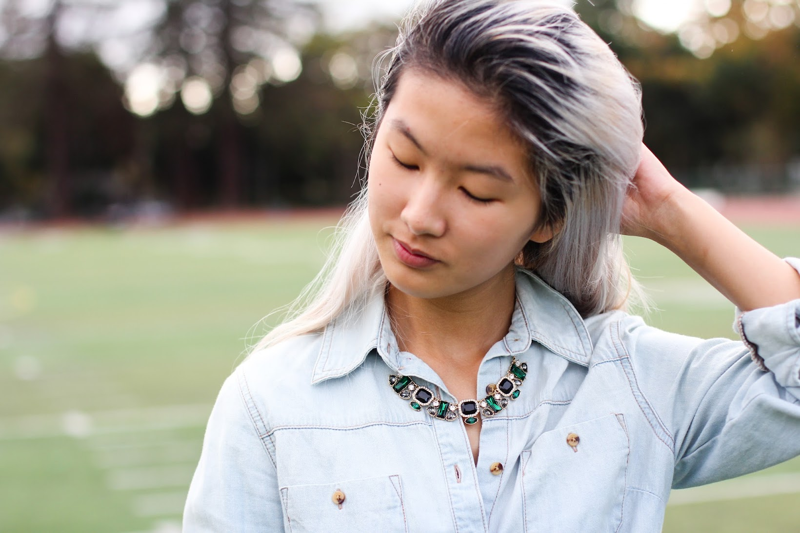 A detail shot of a statement necklace under the collar of a denim top.