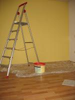 Bild: Eine Leiter steht vor einer gelben Wand, oben auf der Leiter liegt eine Rolle Klebeband. Auf dem Boden liegt eine Plastik Abdeckfolie und darauf steht ein Eimer mit gelber Farbe. Vor der Plastik Abdeckfolie liegt ein Blatt Papier, in Klarsichtfolie.