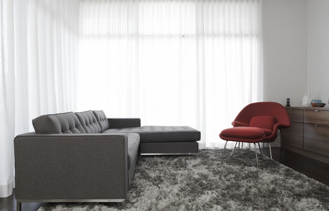 Picture of dark grey sofa and red chair in the grey carpet in the minimalist living room