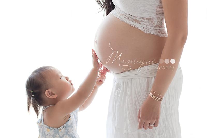 Toddler touching pregnant tummy