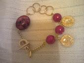 pulseira dourada,pedra vermelha ,elos perola e medalhas