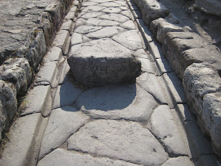 The cartwheel ruts carved into the ancient stone road of Pompeii.
