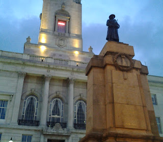 Colour photo of Barnsley Town Hall tower, at early evening. Visible are three arched windows surrounded by pillars, above a balastrade the tower rises up.  In the foreground is a sandstone war memorial surmounted by a bronze of a ww1 soldier resting his rifle in front of him.