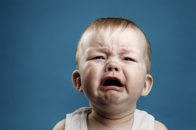صورة بكاء طفل صغير بخلفية زرقاء