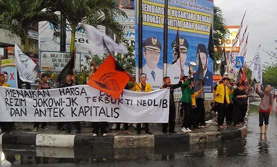 Mahasiswa Hizbut Tahrir Indonesia atau HTI Kalsel kembali turun ke jalan, menggelar aksi menolak kenaikan harga Bahan Bakar Minyak (BBM), Rabu sore (19/11/2014). Aksi di tengah guyuran hujan itu dilakukan di bundaran kantor pos jalan Lambung Mangkurat, Banjarmasin.  Meski diguyur hujan dan diselingi petir tidak menyurutkan semangat para peserta aksi mahasiswa dari berbagai perguruan tinggi negeri maupun swasta yang tergabung dalam mahasiswa HTI Kalsel untuk tetap menyuarakan aspirasi masyarakat.