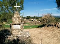 La Creu commemorativa i al seu darrere la masia del Collet del Nado