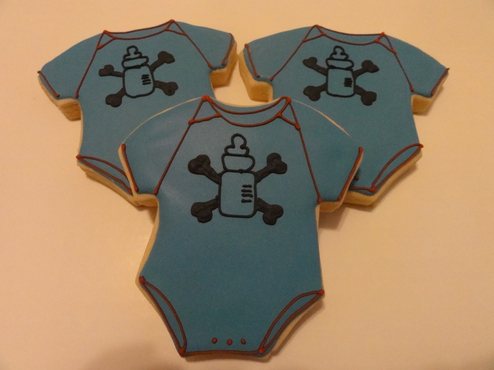 with a bottle and cross bones on it pirate theme baby shower cookies