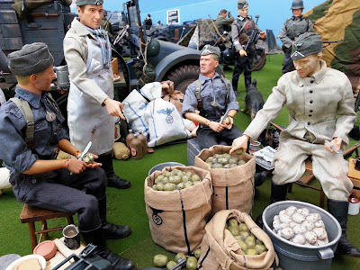 Four 1/6 scale German soldiers peeling potatoes in diorama of an army post on display at a scale model exhibition.