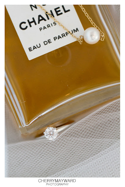 Chanel No. 5 Parfum with necklace and engagement ring, editorial photograph.